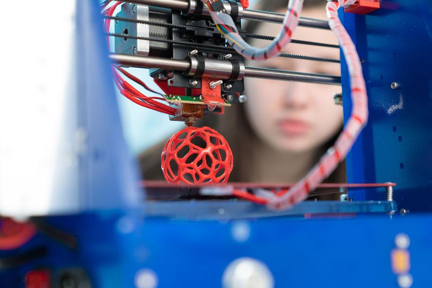 Một phụ nữ trẻ nhìn vào một máy in 3D tạo ra một nguyên mẫu hình quả bóng